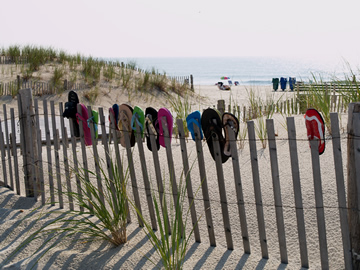 Flip Flops along the barrier fencing at the beach entrance.